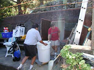 two men moving a 50 gallon drum of wine crush into the fallout shelter in Saratoga California