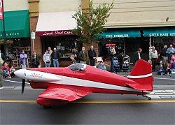 red stunt plane driving down the road in a parade