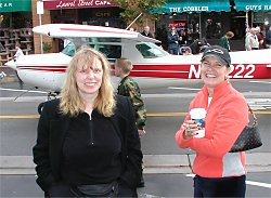 two women standing in front of a plane