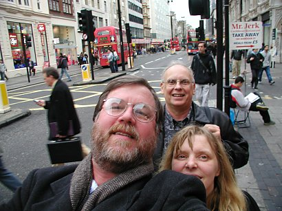 three people looking into the camera on a London street