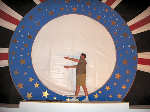 man standing in middle of a blue plate on stage, almost naked