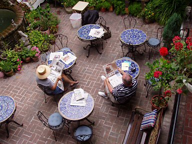 italian courtyard with blue mosaic tiles and two people reading the newspaper