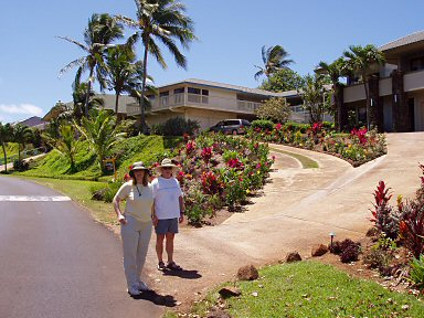 two people standing at the driveway leading up to a house on Pee road, kauai