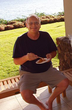 man sitting with a plate of food and a big grin