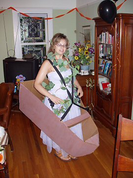 woman in dress and grape vine wearing suspenders and a cardboard boat