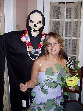 man in skeleton mask with flower lei and a woman wrapped in grape vines with a bottle of wine