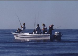 small boat with three fishermen and a captain