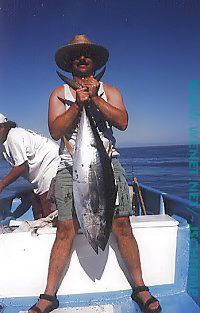 Rick Raives holding up a tuna he just caught