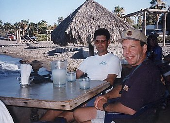 two goofy guys sitting at a table having margaritas
