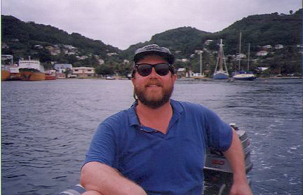 man in a skiff in a harbor in Bequia harbor